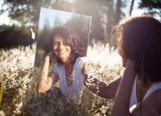 Donna si guarda allo specchio felice e soddisfatta